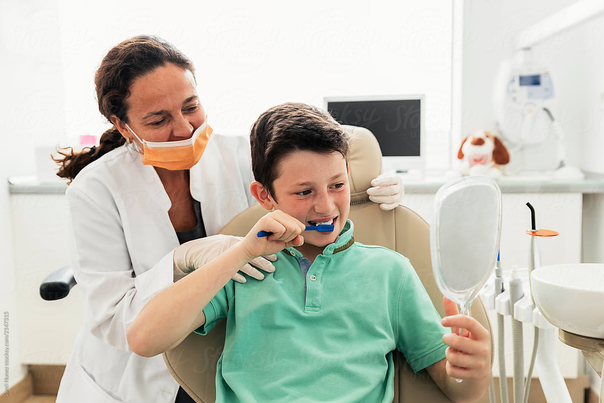 Doctor dentist teaching a child to brush teeth  by Santi