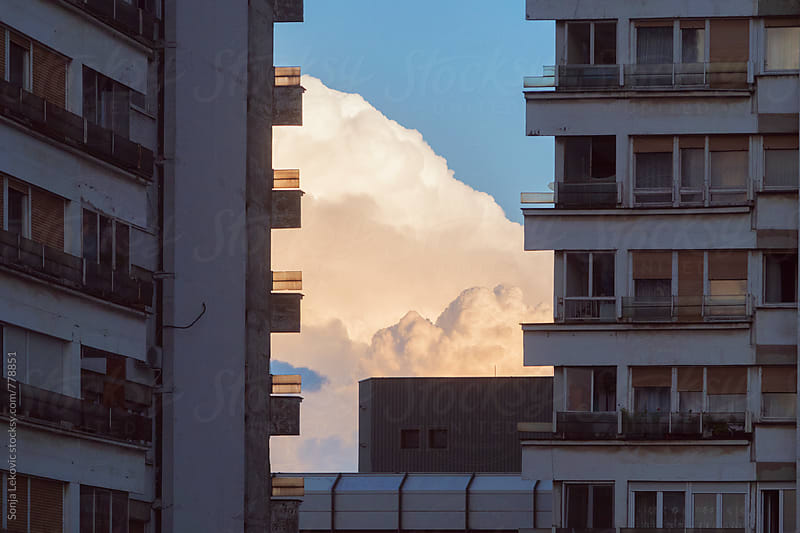 cloud hiding behind the buildings by Sonja Lekovic for Stocksy United