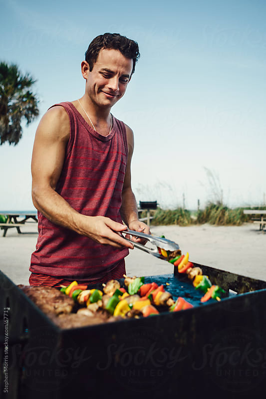 Man Grilling at the Beach by Stephen Morris for Stocksy United
