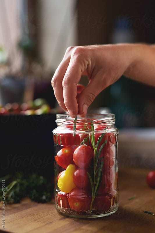 Canning cherry tomatoes and herbs by RG&B Images for Stocksy United