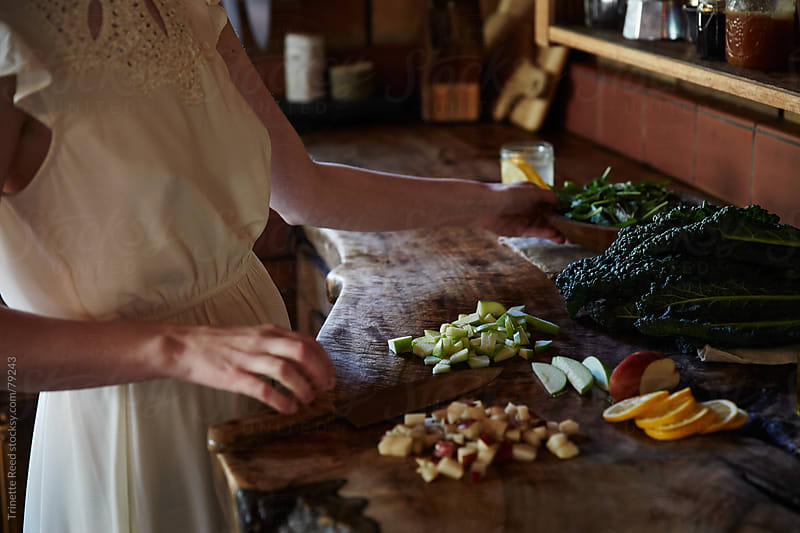 Woman cooking in rustic kitchen by Trinette Reed for Stocksy United