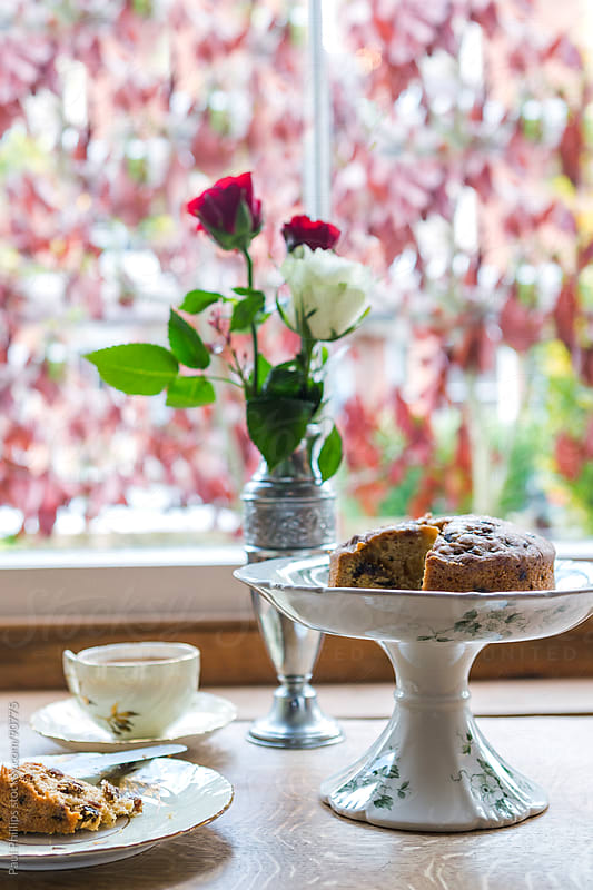Tea and cake by the window by Paul Phillips for Stocksy United