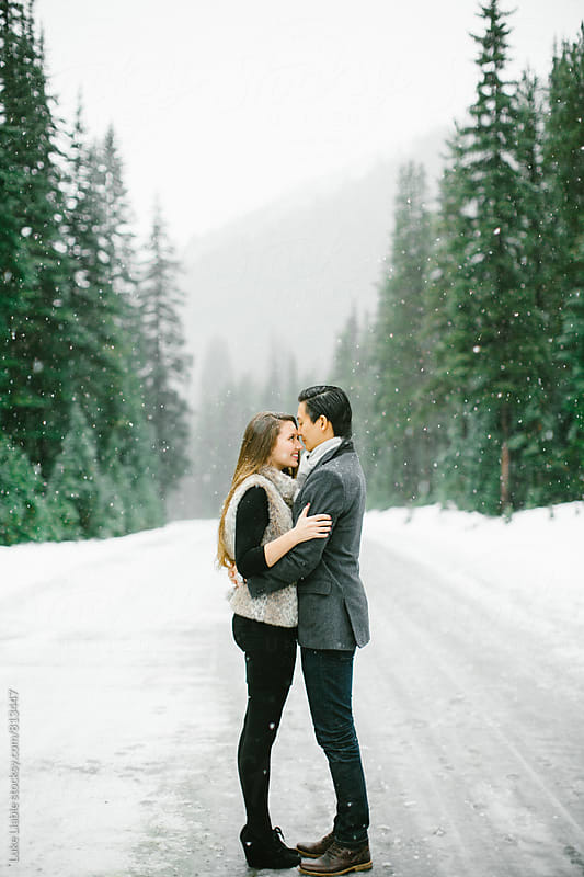 Young engaged couple holding each other in the winter snow. by Luke Liable for Stocksy United
