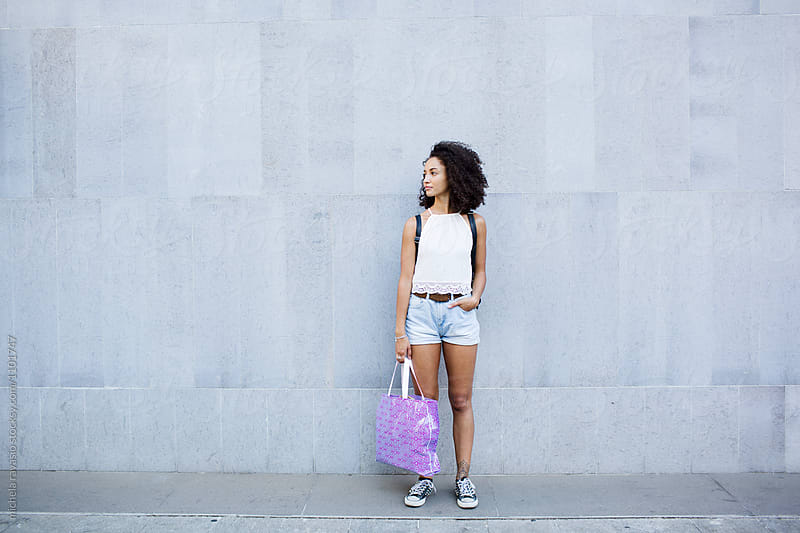 Young woman standing in front of the wall with daypack and a bag. by michela ravasio for Stocksy United