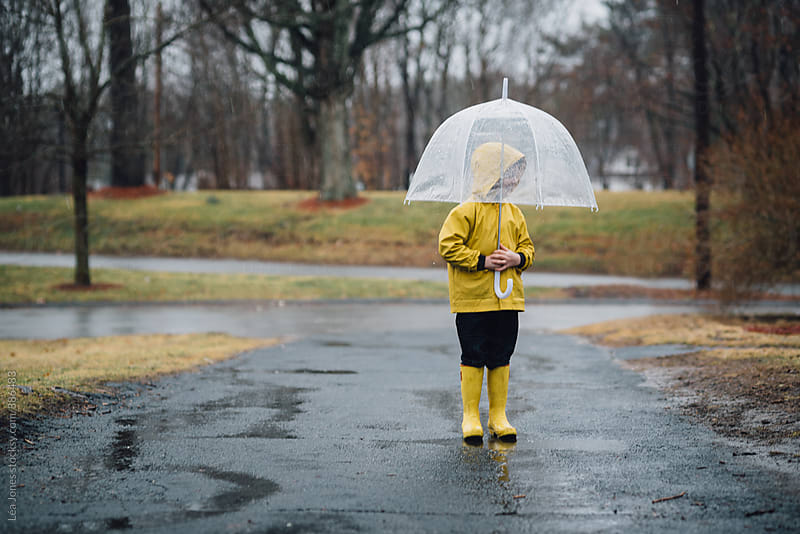 little boy in yellow raincoat and yellow boots stating under umbrella by Léa Jones for Stocksy United