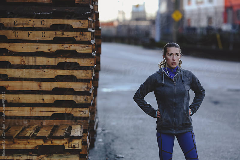 Young, healthy caucasian woman breathing hard outside during running workout by Rob and Julia Campbell for Stocksy United