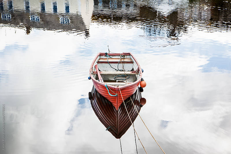 A moored boat in a tranquil harbor by James Ross for Stocksy United