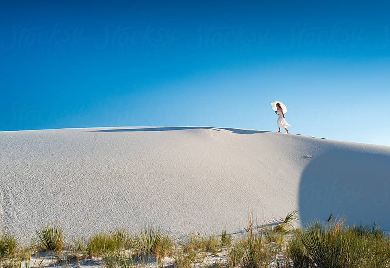 Woman Walking Along Crest of Sand Dune With Sun Umbrella In White Sands National Monumant New Mexico by JP Danko for Stocksy United