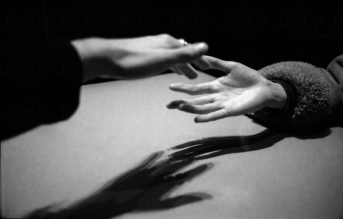Black and white photograph of two hands almost touching