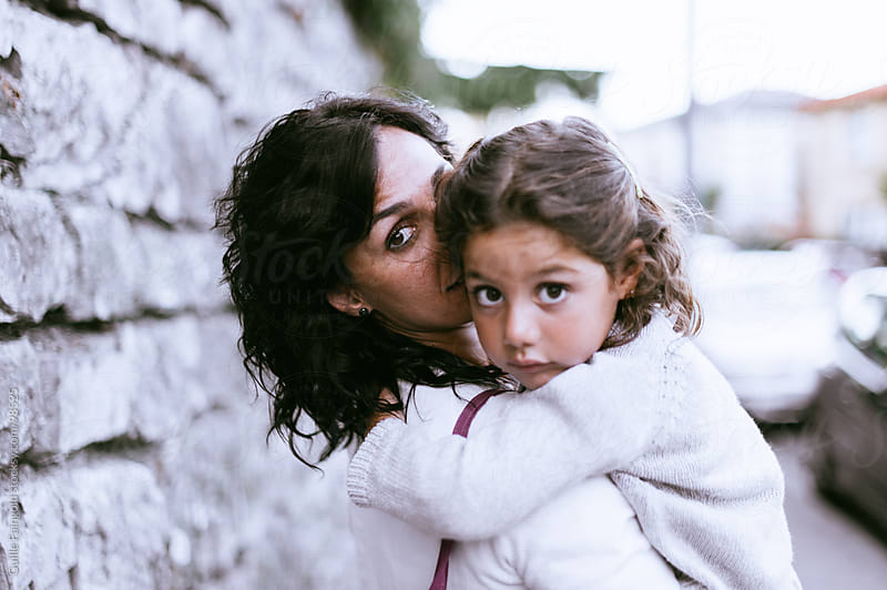 Tired little girl in her mother's arms by Guille Faingold for Stocksy United