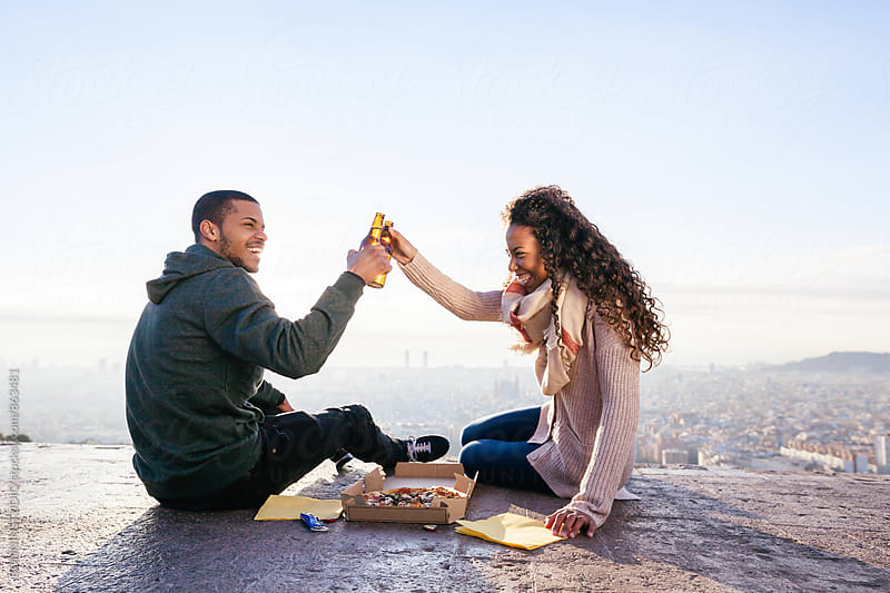Smiling couple cheering with beer above Barcelona. by BONNINSTUDIO for Stocksy United