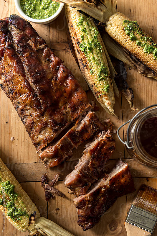Close-up of tasty BBQ ribs with sweet pesto corn by Trent Lanz for Stocksy United