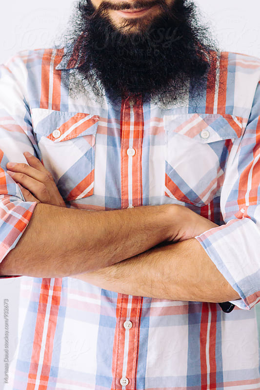 A portrait of a bearded man with his arms folded by Murtaza Daud for Stocksy United