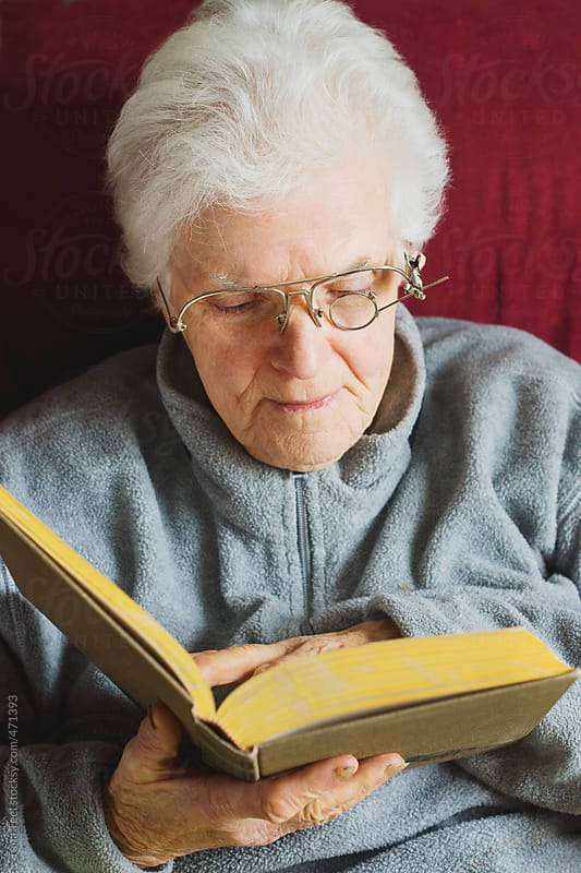 Older woman reading book with homemade eyeglasses by Tana Teel for Stocksy United
