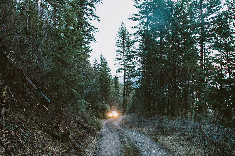 Car with headlights on steep mountain road.  by Justin Mullet for Stocksy United
