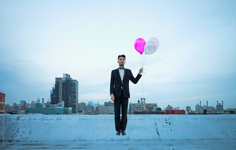Young Man in a Suit Carried by Balloons from Rooftop in New York by Joselito Briones for Stocksy United