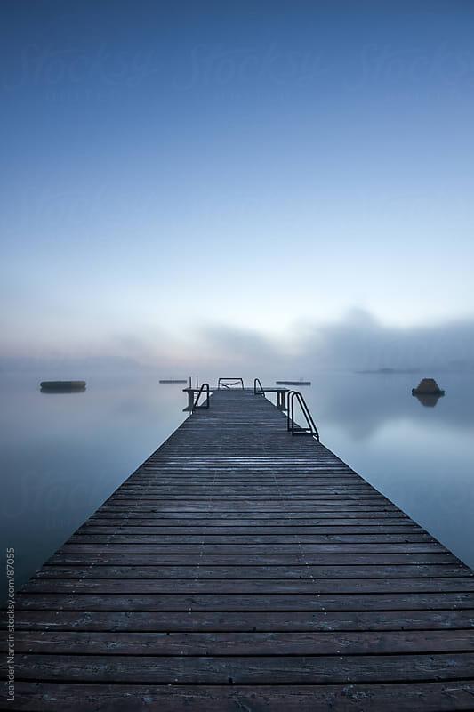 wooden dock in morning fog at sunrise by Leander Nardin for Stocksy United