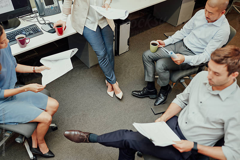 Overhead view of colleagues sitting in casual business meeting by Aila Images for Stocksy United