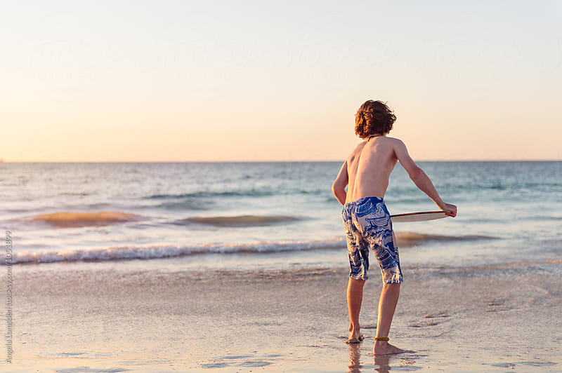 Boy about to launch himself onto a skim board at the beach at sunset by Angela Lumsden for Stocksy United