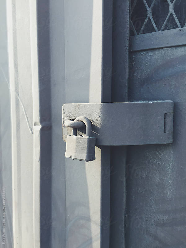 Padlock on metal warehouse door by Paul Edmondson for Stocksy United