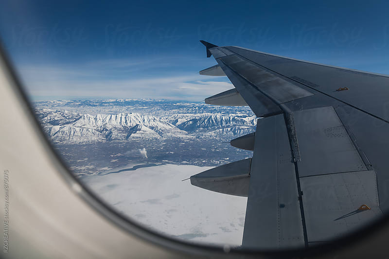 View of snowy mountain range from window seat. by RZ CREATIVE for Stocksy United