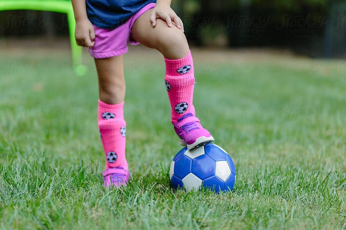 8beb25a35 Young girl standing with one foot on top of a soccer ball by Jakob  Lagerstedt for