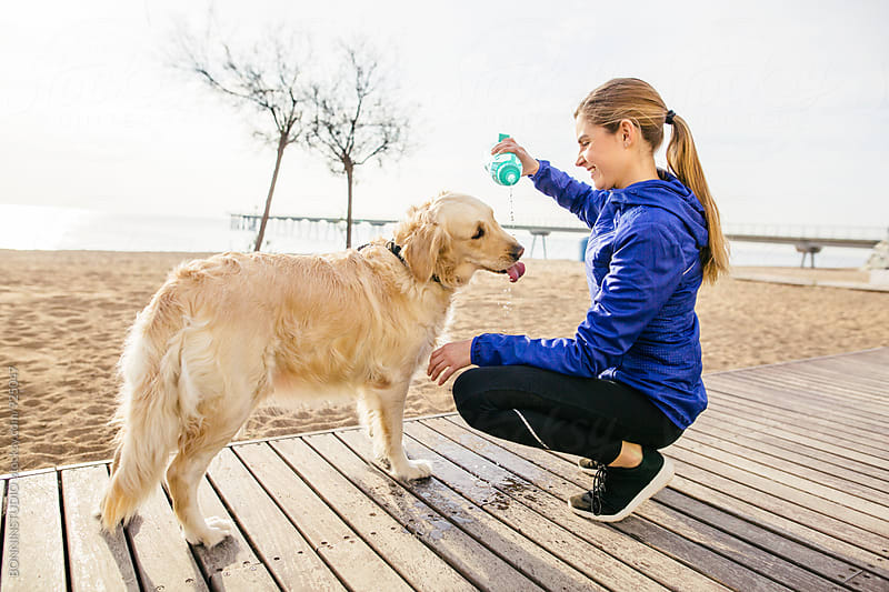 Runner woman gives water to her dog after workout. by BONNINSTUDIO for Stocksy United
