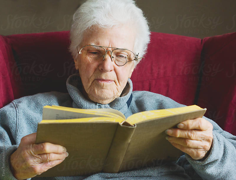 Older woman holding book reading with homemade eyeglasses by Tana Teel for Stocksy United
