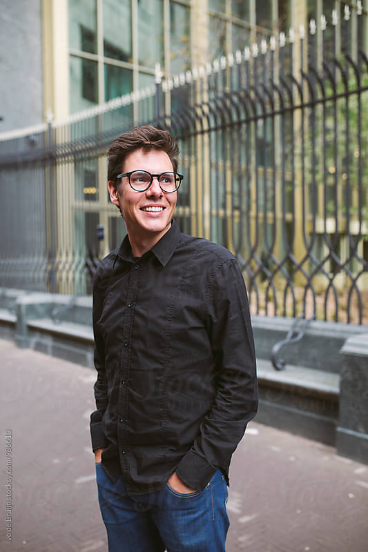 Portrait of a young man with glasses and a black shirt, smiling. by Ivo de Bruijn for Stocksy United
