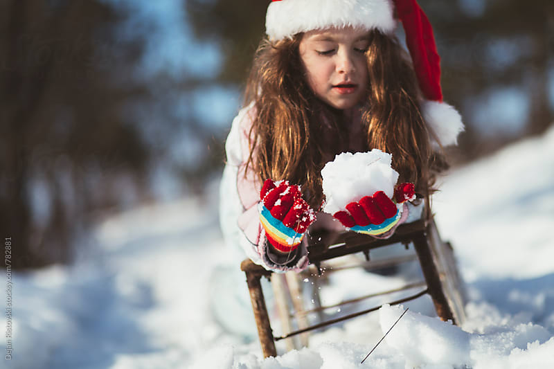 Child playing with snow by Dejan Ristovski for Stocksy United