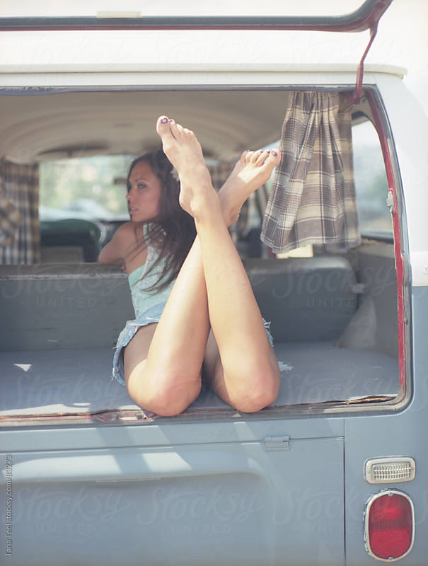 Woman wearing shorts lays on her stomach with her ankles crossed out the back of an old van by Tana Teel for Stocksy United