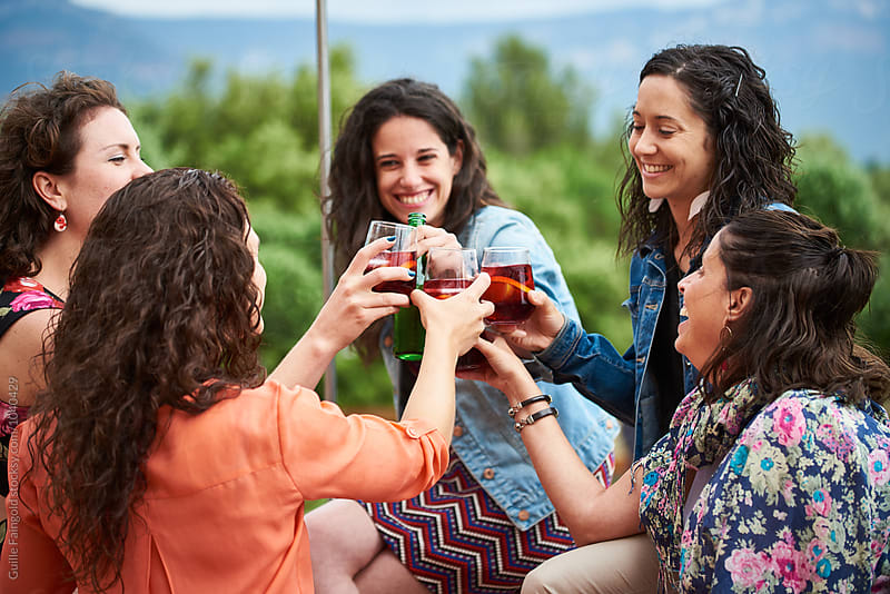 Smiling girlfriends cheering with drinks in garden by Guille Faingold for Stocksy United