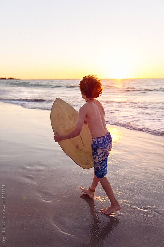 Boy viewed from behind about to launch himself off onto a skim board at the ocean's edge at sunset by Angela Lumsden for Stocksy United