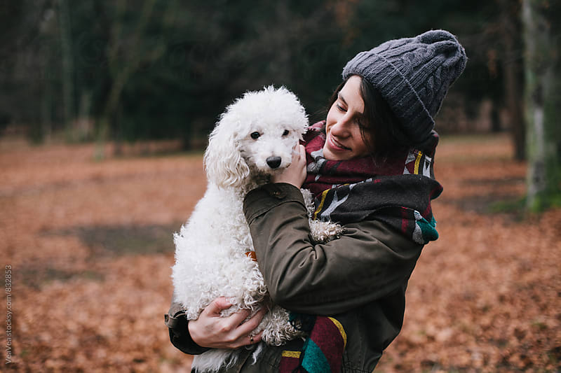 Beautiful woman having a good time with her dog outdoors by Marija Mandic for Stocksy United