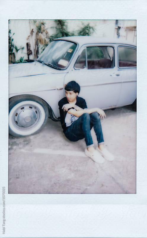 Polaroid portrait photo of a young Asian man sitting by the old car in bangkok by Nabi Tang for Stocksy United