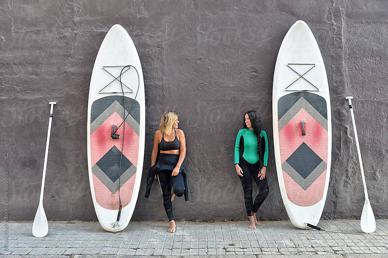 Two friends with their paddle boards on a black wall in Barcelona beach by Bisual Studio for Stocksy United