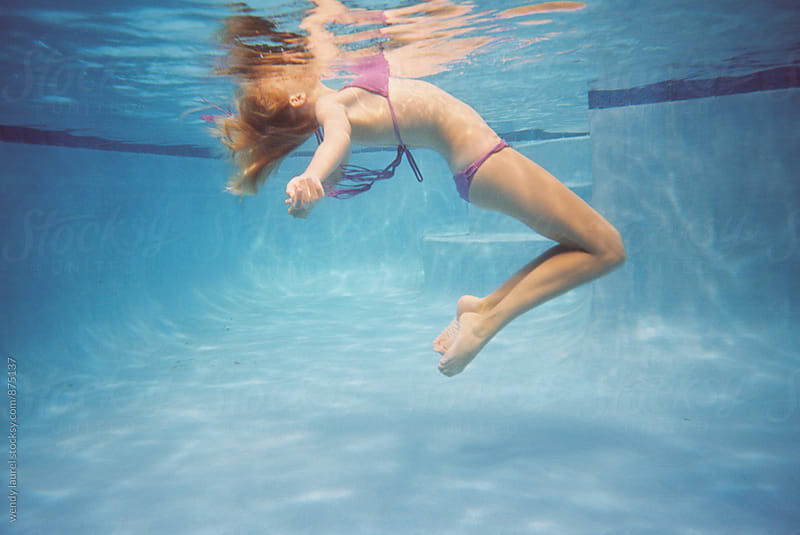 girl floating in pool in bikini underwater by wendy laurel for Stocksy United