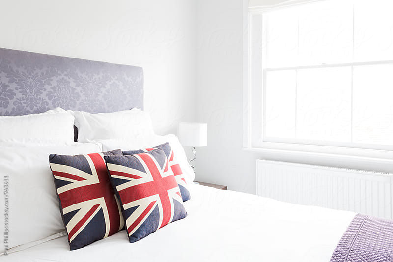 Bedroom with cushions showing the Union Jack ( the national flag of the UK ) by Paul Phillips for Stocksy United
