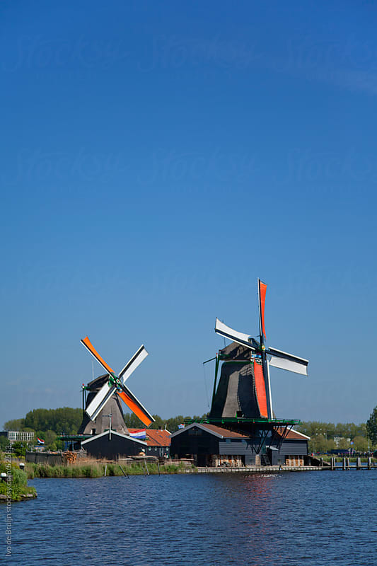 Two classic windmills standing along a dutch canal  with their wings in the sun by Ivo de Bruijn for Stocksy United