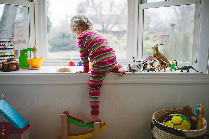little girl in pajamas playing with toys on a window sill by Meaghan Curry for Stocksy United