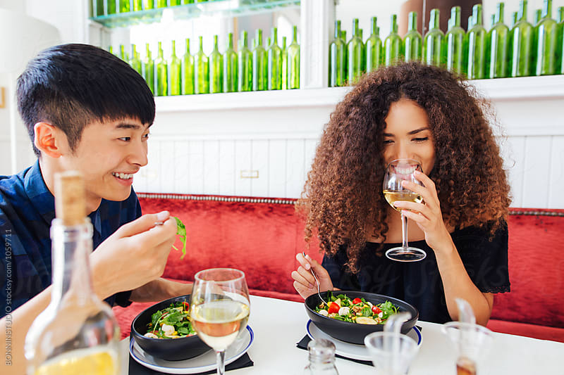 Smiling multi-ethnic couple eating a heathy meal in a cool restaurant.  by BONNINSTUDIO for Stocksy United