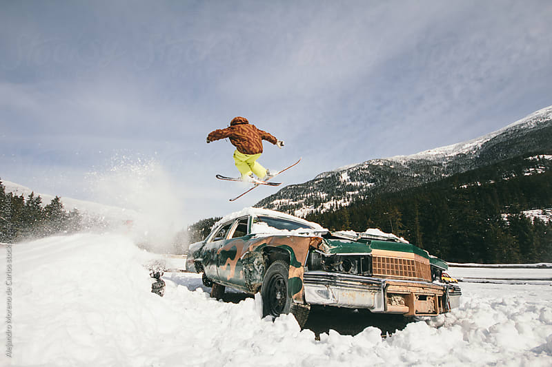 Skier jumping over old vintage abandoned car. Freestyle urban sk by Alejandro Moreno de Carlos for Stocksy United