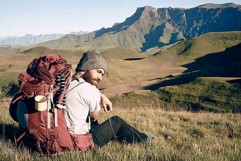 Male hiker with his back pack taking a break in a field surrounded by mountains. by Jacques van Zyl for Stocksy United