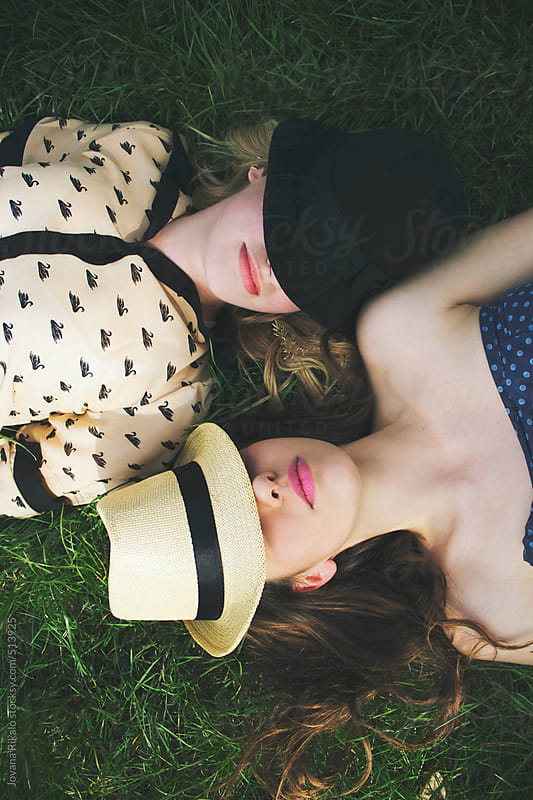 Two female friends with hats  lying on grass  by Jovana Rikalo for Stocksy United
