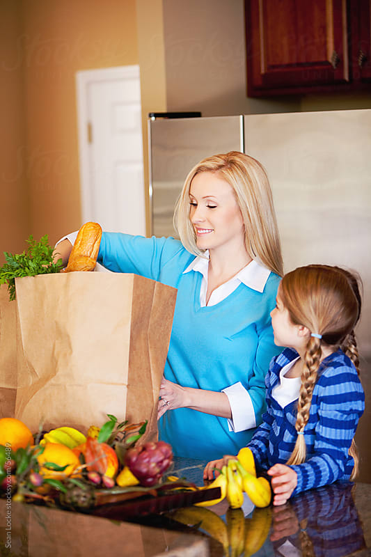 Family: Girl Helps Mother Put Away Groceries by Sean Locke for Stocksy United