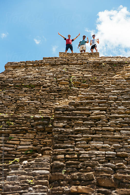 Three friends at the top of ancient pre-columbian ruins on a sunny day during their vacation travel by Alejandro Moreno de Carlos for Stocksy United