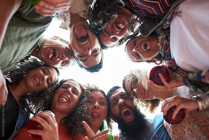 Below view of young happy people with drinks having fun at party by Guille Faingold for Stocksy United