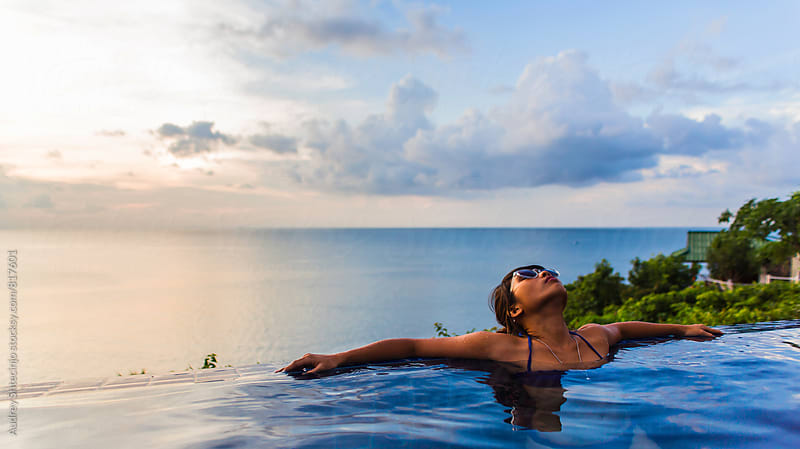 Woman relaxing at the edge of swimming pool with sea horizon and sky in background during sunset. by Audrey Shtecinjo for Stocksy United