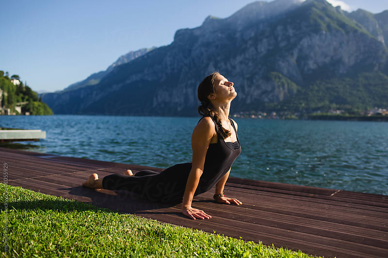 Woman doing yoga pose: Urdhva Mukha Svanasana by michela ravasio for Stocksy United