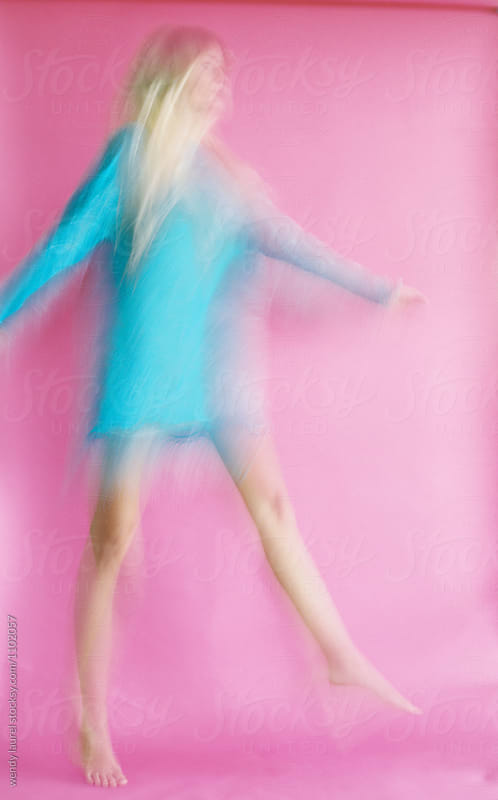 blonde girl in blue dress blurred against pink background by wendy laurel for Stocksy United